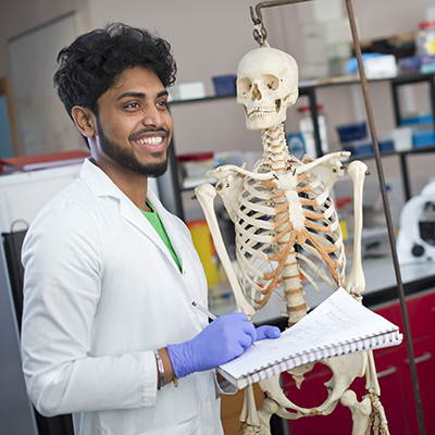 Biomedical Sciences student with a skeleton