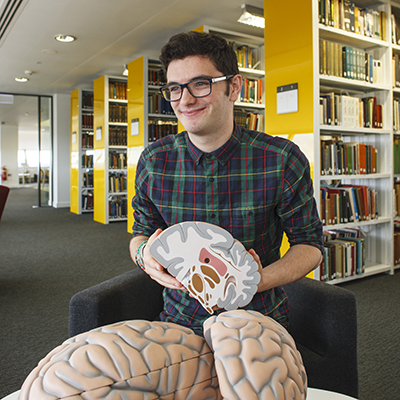 Student in the library with models of brains