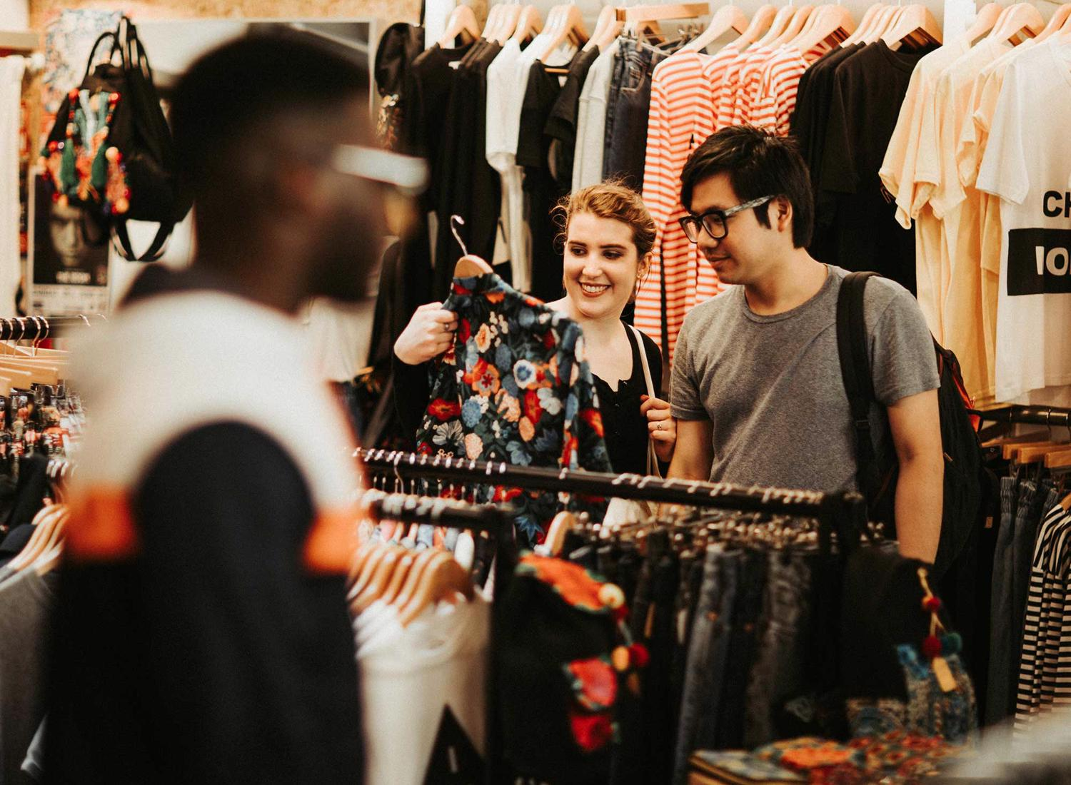 A student couple look at an item of clothing in a vintage clothes shop in Hull