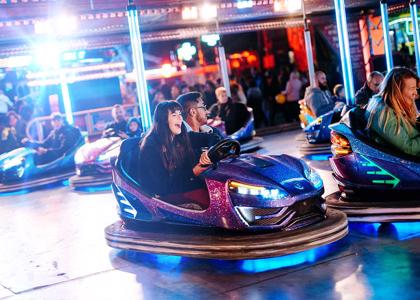 Two students laugh while crashing into another cart on the dodgems at Hull Fair.