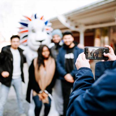 Four friends pose with Pride the Lion, Team GB's mascot, for a photo outside Hull University Union.