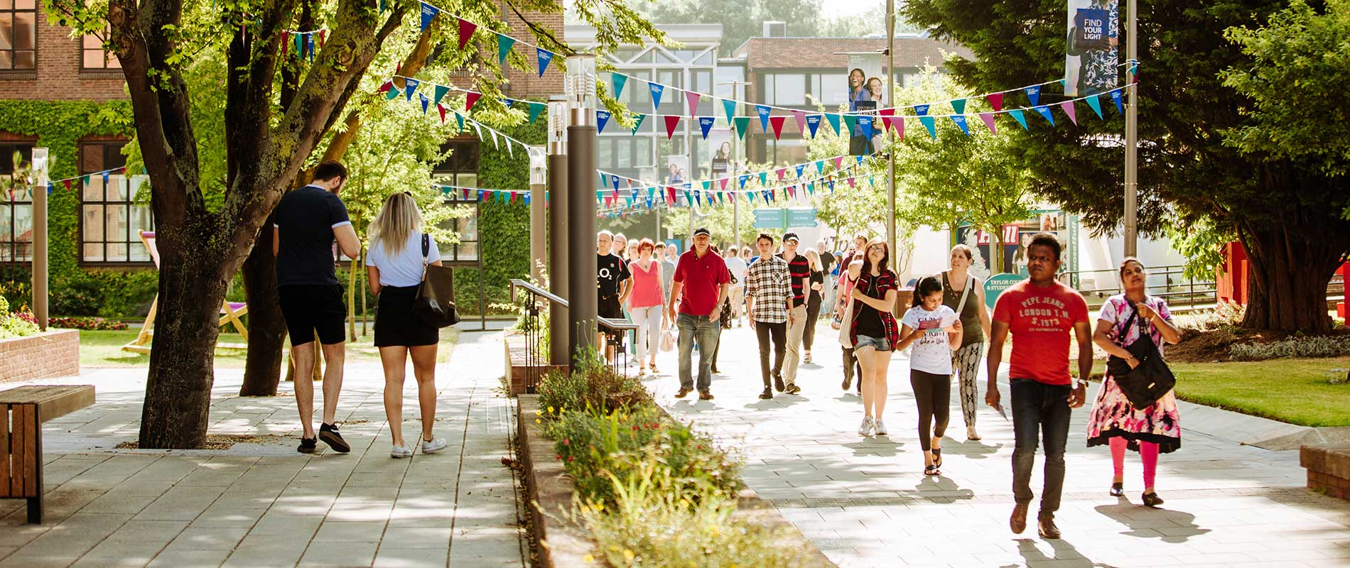 A group of smiling people walk through the University of Hull's campus, through trees with colourful bunting overhead.