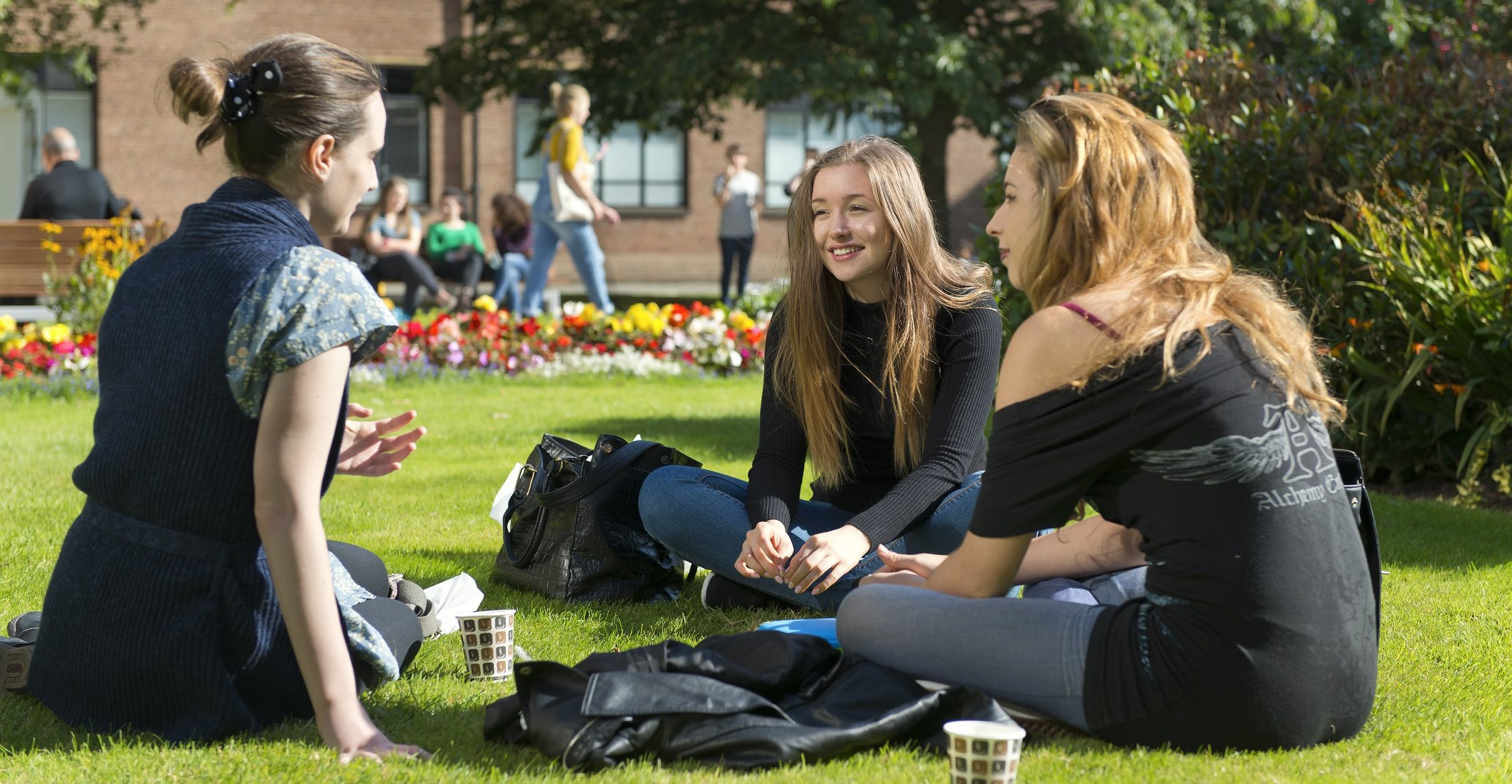 Female Students sat on Campus Lawn Landscape